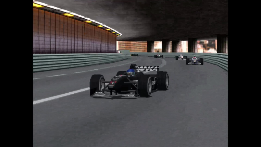 A black F1 car driving through an underpass, with several other cars in tow.